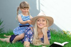 Mom blonde in a hat and her daughter are lying on the grass and reading a book, happy family. stock image