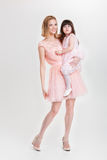 Mom blonde holding cute little daughter in pink Princess dress o Stock Photo