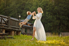Mom blonde in white dress laughs and spins son at sunset in summ Stock Photo