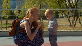 Mom blows soap bubbles. Baby looking how she do it. Summer day in the park. Slow motion stock footage