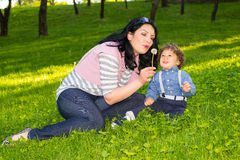 Mom and boy blowing out dandelion Royalty Free Stock Photos