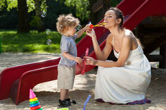 Mom and boy making bubbles Stock Image