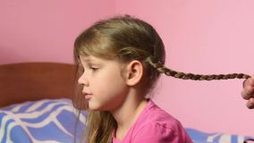 Mom braided pigtail daughter and kissed her on cheek stock video footage