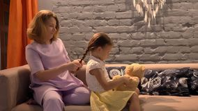 Mom braiding and taking care of her little daughter`s hair, parent and kid sitting together on couch at modern home stock footage
