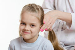 Mom braids tails of hair six-year daughter Stock Photos