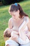 Mom breast feeding girl Royalty Free Stock Photo