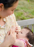 Mom breast feeding her baby girl Stock Photo