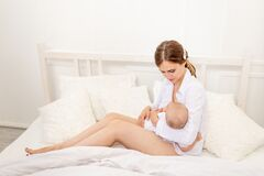 Mom breastfeed baby 6 months old lying on a white bed, baby feeding, place for text