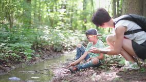 Mom brought her son a paper boat. On a stream in the summer stock footage