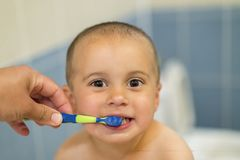 Mom brush cleans teeth funny kid 2 years stock photo