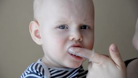Mom brushes baby`s teeth with a brush that fits on her finger stock footage
