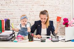Mom and businesswoman working with laptop computer at home and playing with her baby girl. Stock Image