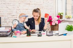 Mom and businesswoman working with laptop computer at home and playing with her baby girl. Stock Images