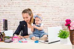 Mom and businesswoman working with laptop computer at home and playing with her baby girl. Royalty Free Stock Photos