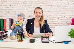 Mom and businesswoman working with laptop computer at home and playing with her baby girl. Horizontal shape, front view, waist up Royalty Free Stock Image