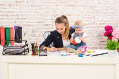 Mom and businesswoman working with laptop computer at home and playing with her baby girl. Horizontal shape, front view, waist up Stock Image