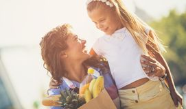 Mom always cares to keep healthy. Mother and daughter on street with fresh fruit. Copy space. Close up stock photography