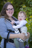 Mom carrying baby girl with carrier, enjoying the day in the park Royalty Free Stock Photography