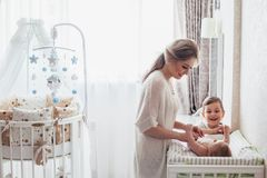 Mom changing diaper to baby. Bright portrait of a mom changing a diaper to her baby royalty free stock images