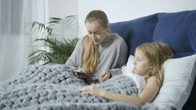 Mom checking teen daughter`s temperature in bed. Sick cute blond little daughter got flu and has fever. Mother sitting with her on bed, checking girl`s stock video