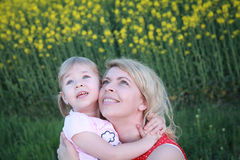 Mom and chil standing in rapeseed field and looking up Stock Photos