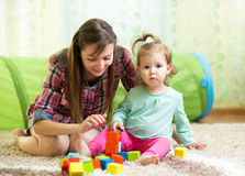 Mom and child daughter play block toys home Stock Photos