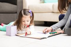 Mom And Child Drawing On Paper. Caucasian girl drawing with crayons while mother assisting her in living room stock photography