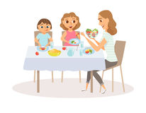 Mom and child eating. Meal around kitchen table. Happy mother and her two kids sitting eating healthy lunch in home. Smiling woman feeds her daughter and son Royalty Free Stock Image