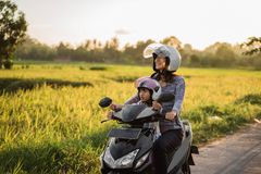 Mom and child enjoy riding motorcycle scooter royalty free stock images