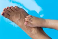 Mom and child feet above the water stock images