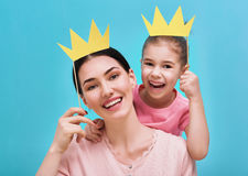 Mom and child are holding crown. Funny family on a background of bright blue wall. Mother and her daughter girl with a paper accessories. Mom and child are Stock Image