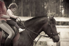 Mom and child on the horse. Mom and child horseback riding Royalty Free Stock Image