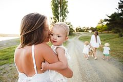Mom and the child. The kid is sitting with his mother in his arms while walking in nature. stock photography