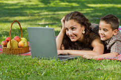 Mom and child with  laptop outdoors Stock Image
