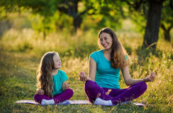 Mom and child in the lotus position. On the nature Stock Images