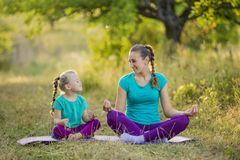 Mom and child in the lotus position. On the nature Royalty Free Stock Image