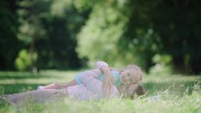 Mom And Child Lying And Hugging On Grass In Park stock video