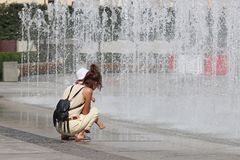Mom and the child near the refreshing splashes of the summer city fountain. Bathing and rest in your free time in the rays of the stock image