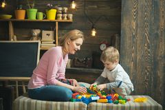 Mom and child play with details of constructor, plastic bricks. Nursery with chalkboard on background. Mother and son royalty free stock photo