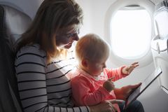 Mom and child playing tablet while flying on plane. Mom and child playing ipad while flying on plane Stock Photos