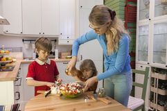 Mom and child pouring the salad with olive oil. Kids helping mother on the kitchen Royalty Free Stock Photos
