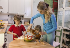 Mom and child pouring the salad with olive oil. Kids helping mother on the kitchen Stock Photography