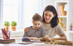 Mom and child reading a book. Pretty young mother and her cute daughter are reading a book. Learning to read at home Stock Photography