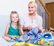 Mom and child with sew. Portrait of happy young mom and child with sewing kit Royalty Free Stock Photography