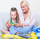 Mom and child with sew. Portrait of positive mom and child with sewing kit at home Royalty Free Stock Photos
