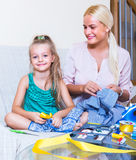 Mom and child with sew. Portrait of smiling young mom and child with sewing kit at home Stock Image