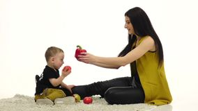 Mom and child are sitting on the floor, around a lot of vegetables and fruits. White background. Slow motion stock video footage