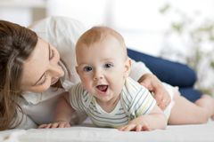 Mom and little son lying down on bed. Mother embracing infant baby. Mom and child son lying down on bed. Mother embracing infant baby Stock Image
