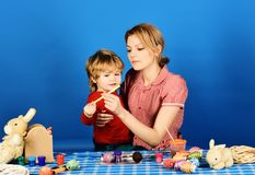 Mom and child spend time together. Family happiness concept. Mother holds son on blue background. Woman and little boy with cheerful smiles stock photo