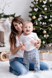 Mom with a child under the Christmas tree Stock Photo